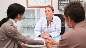 Doctor sitting at her office speaking with patients