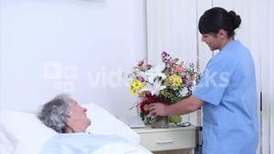 Serene senior woman speaking at a nurse who gives a bouquet of flowers