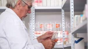 Pharmacist looking at pills in a shelf with a clipboard