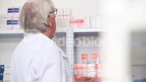 Pharmacist looking at pills in a shelf