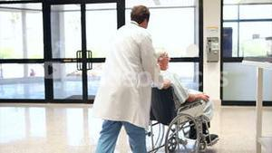 Patient in a wheelchair pushing by a doctor