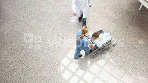 High angle view of a medical team wheeling a patient in a wheelchair
