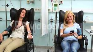 Patient receiving a blood transfusion while holding a smartphone