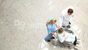 High angle view of a nurse wheeling a patient in a wheelchair