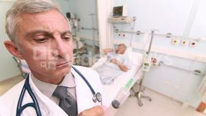 Serious doctor with an injection in his hands in a room