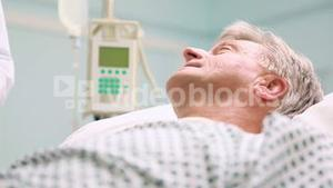 Doctor holding a chart in a bed ward
