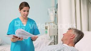 Smiling nurse talking with a patient lying on a bed while holding a paper