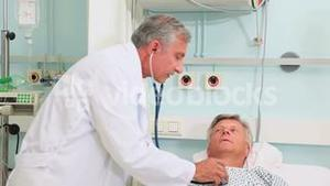 Male doctor auscultating a male patient in a bed ward
