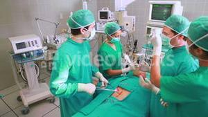 Surgeons operating a patient belly