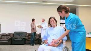 Nurse pushing a pregnant woman in a wheelchair