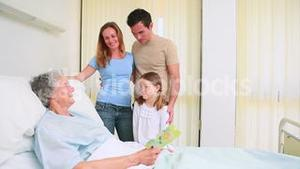 Family standing together around a hospital bed while a patient is reading a card