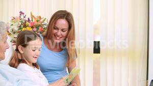 Smiling mother and girl sitting on the bed of a patient