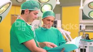 Two surgeons smiling while holding files in a surgery theater