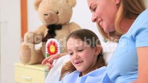 Mother with her daughter in a hospital ward looking at a card