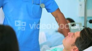 Male nurse talking to a patient with a doctor