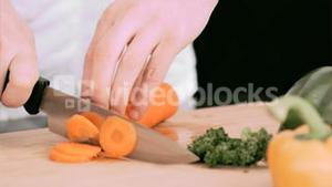 Woman cutting a carrot into slivers in slow motion