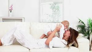 Woman playing with a baby on the sofa