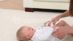 Baby laughing when woman playing with him