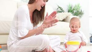 Baby putting a green dice into bucket and woman applauds