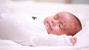 New born baby in diapers lying on a bed with blankets