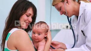 Mother holding a baby in an examination room with a smiling doctor using a stethoscope
