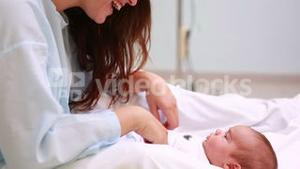 Mother sitting on a bed while smiling to a new born baby