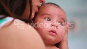 Woman kissing a baby in diaper