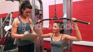 Trainer talking to woman on weights machine