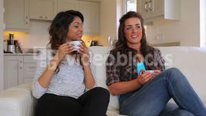 Friends sitting on the couch drinking coffee