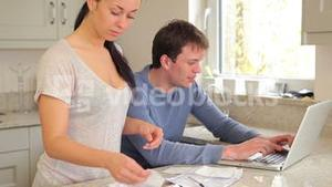 Couple working out bills on laptop