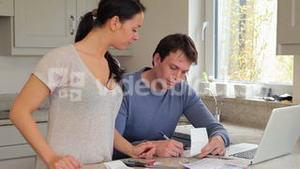 Couple checking bills with the laptop