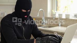 Burglar hacking laptop