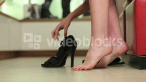Woman sitting down and trying on shoes