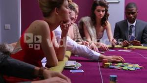 People at poker table placing bets woman in red dress going all in