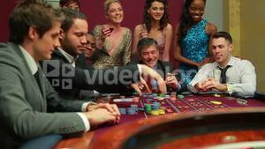 Men placing bets at roulette table watched by women