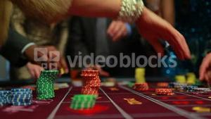 People placing their bets on roulette table