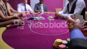 Man looking at his amazing poker hand and betting his house