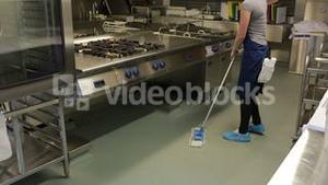 Cleaner wiping the floor in a kitchen