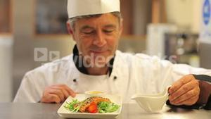 Smiling chef pouring dressing over salmon dish