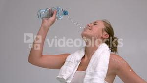 Woman pouring bottle of water on her face