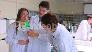 Scientist group studying beaker of green liquid