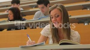 Woman sitting while smiling and taking notes