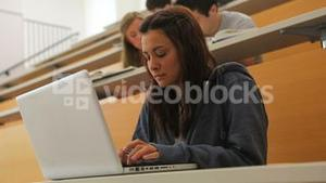 Student using laptop in lecture hall