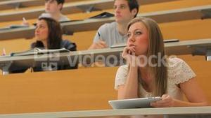 Student sitting at the lecture hall holding a tablet pc