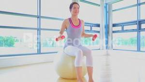 Woman sitting on a exercise ball with dumbells