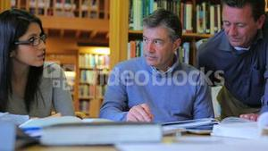 Men and woman talking in library