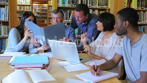 People in library looking at laptop