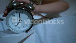 Waking up woman pushing down the alarm cock