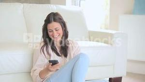 Brunette woman phoning in the living room