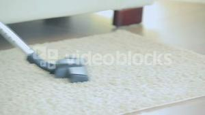 Video of woman hoovering rug